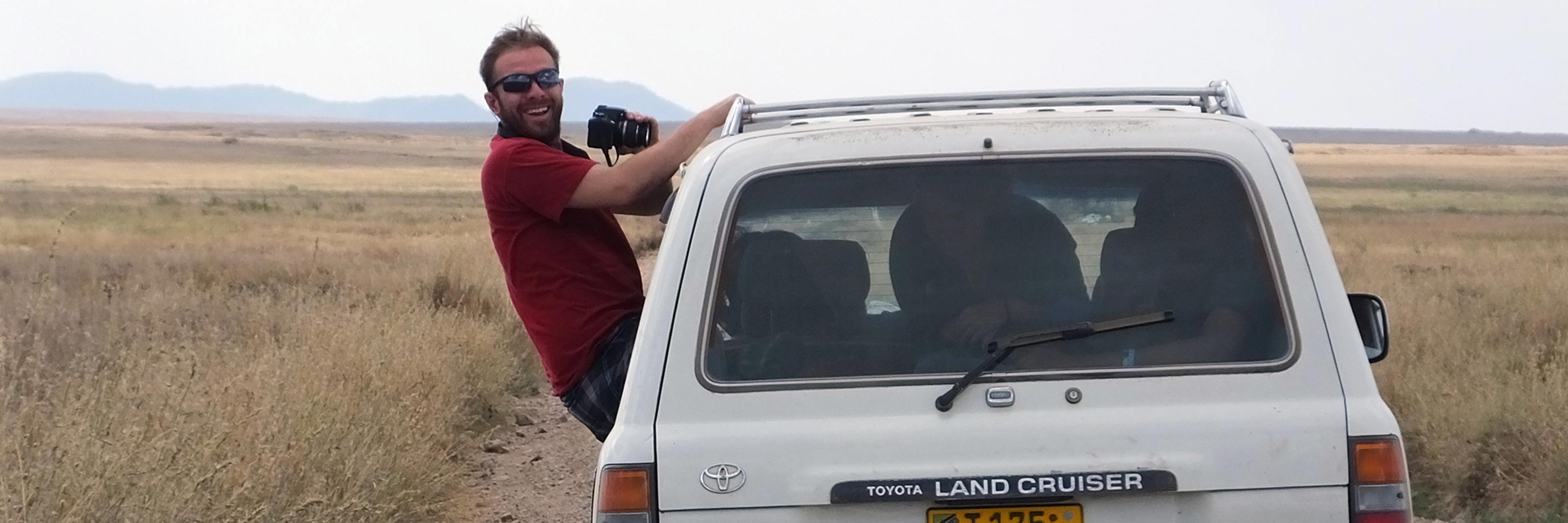 Student leaning out of a vehicle to take photos for field research