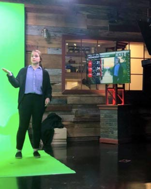 Sarah McCorkle standing in front of a green screen to report on the weather
