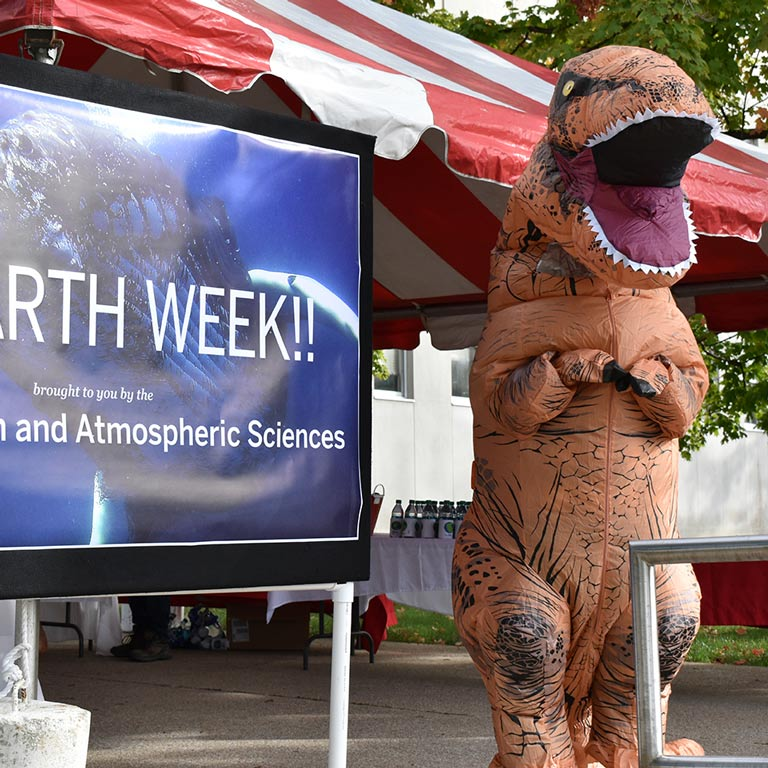 "Department mascot, a T. Rex, poses with a sign for ""Earth Week"""