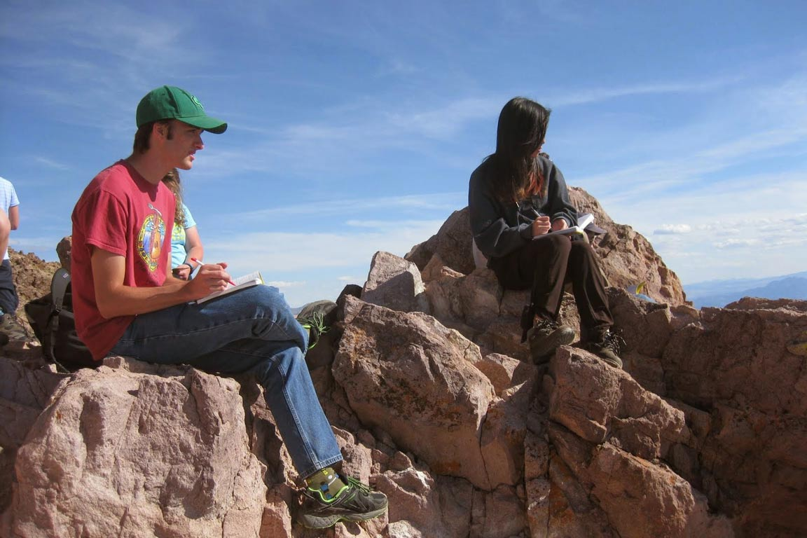 Two students perched on boulders taking notes