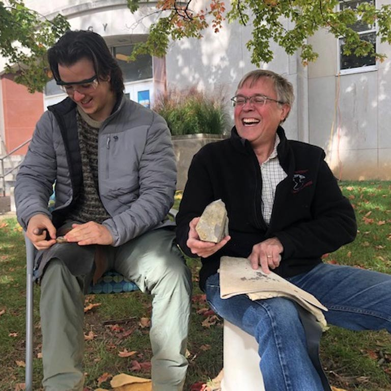 Two men sitting outside laughing