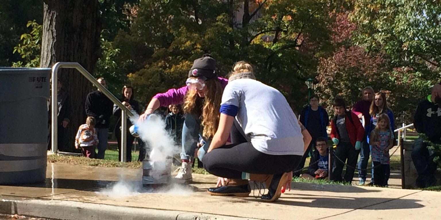 Two students performing an experiment with dry ice
