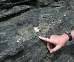Finger pointing at a large rock formation