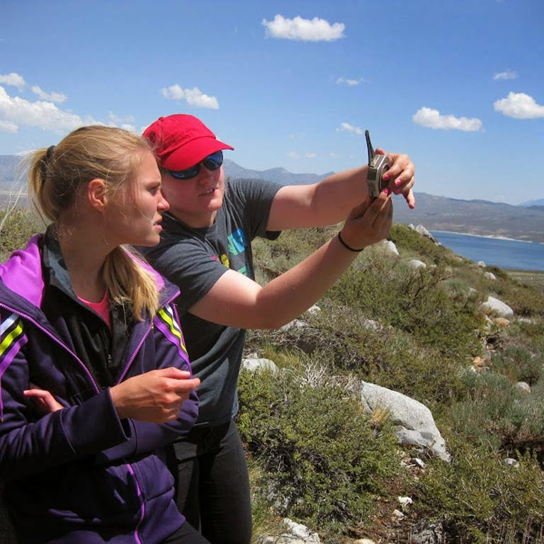 Two students using a compass for field research