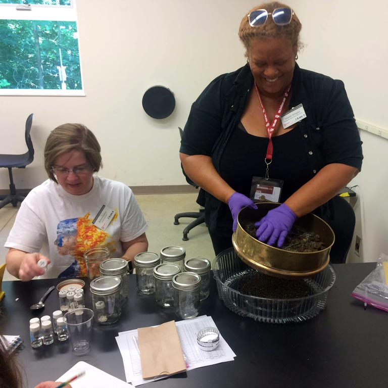 Two women handling a variety of equipment for a scientific experiment