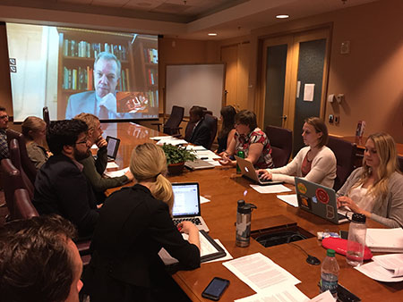 People in a conference room with computers listening to a conference on a projector screen