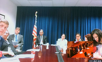 Screenshot of a web conference of people sitting around a conference table with American flag in background