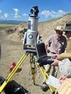 Geologists stand next to camera and instrumentation equipment outside