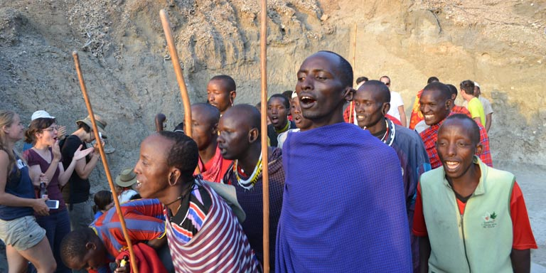 Students observing locals perform the maasai dance in Tanzania