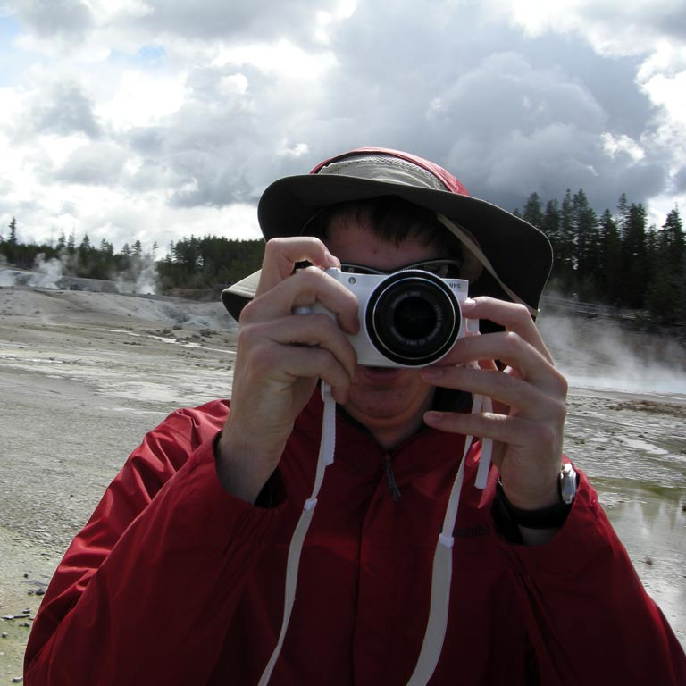 Man holding a camera in front of his face to take a picture