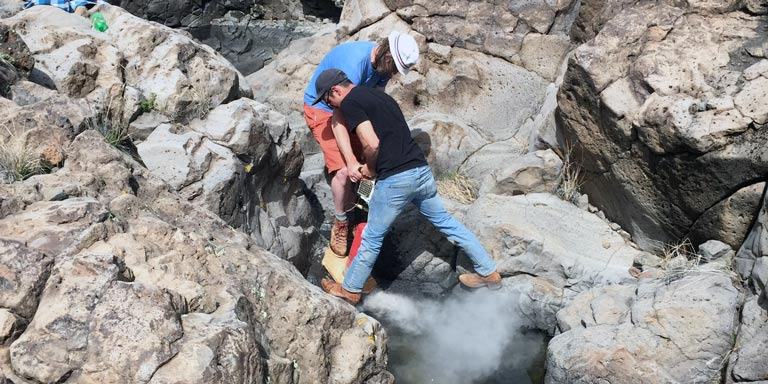 Two men using mechanical equipment to break up rocky landscape