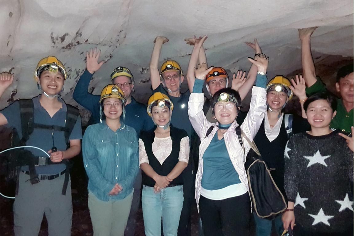 Group of people smiling for the camera in a cave