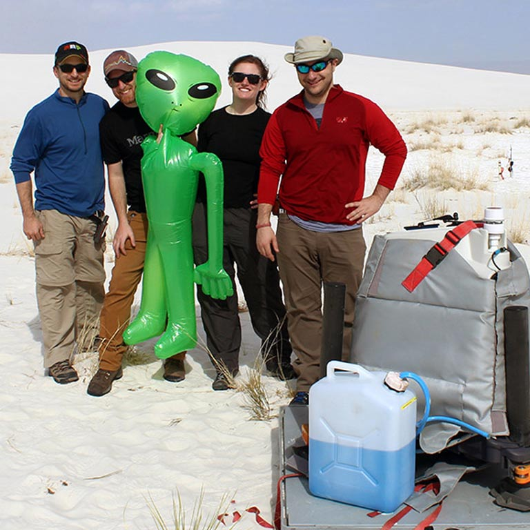 Four people out in the field posing with a blow-up alien